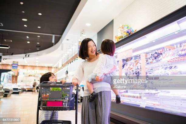 Young girl helping her mother by pushing the shopping cart