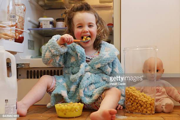 Young girl helping herself to cereal and milk