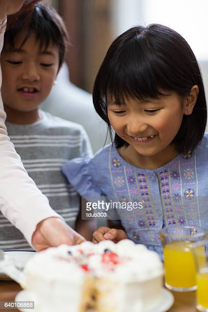 Young girl helping to serve cake at a family celebration