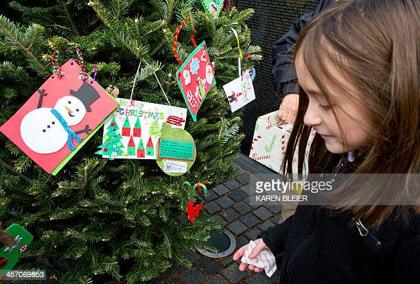 A young girl helps to decorate a Christmas Tree at the Vietnam Veterans Memorial Wall on December 16 2013 in Washington DCThe Vietnam Veterans...