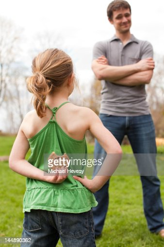 A young girl hiding a cookie from her father : Stock Photo