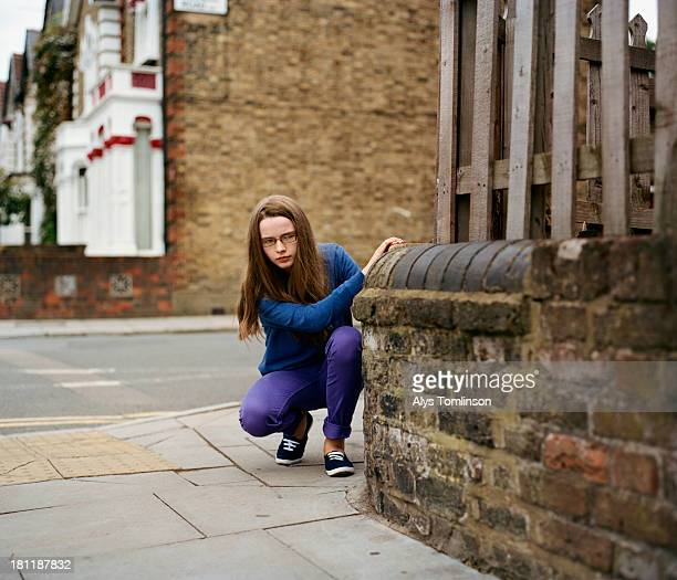 Young girl hiding behind a wall outdoors