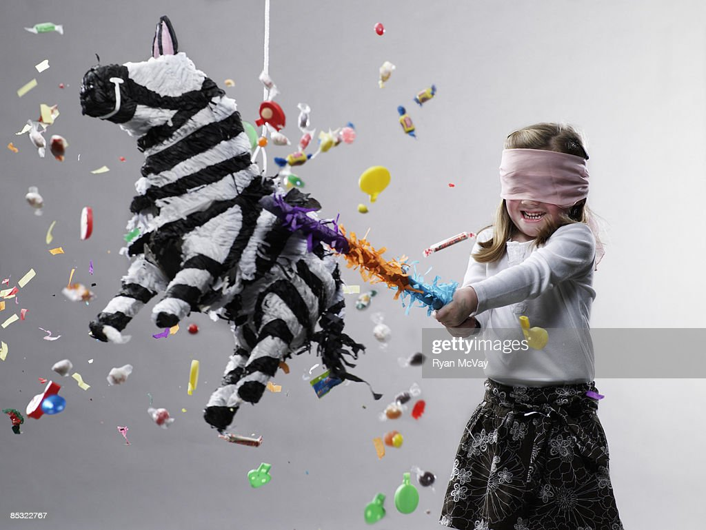 Young girl hitting pinata, candy flying : Stock Photo