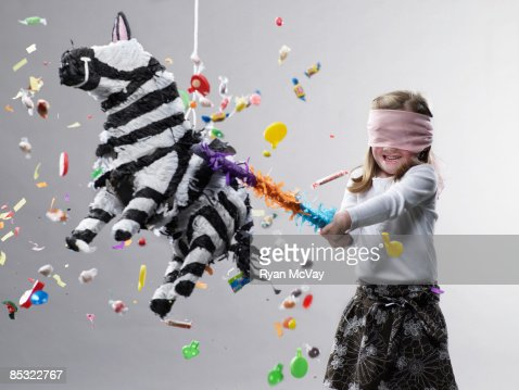 Young girl hitting pinata, candy flying : Bildbanksbilder