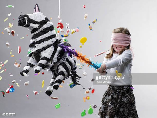 Young girl hitting pinata, candy flying