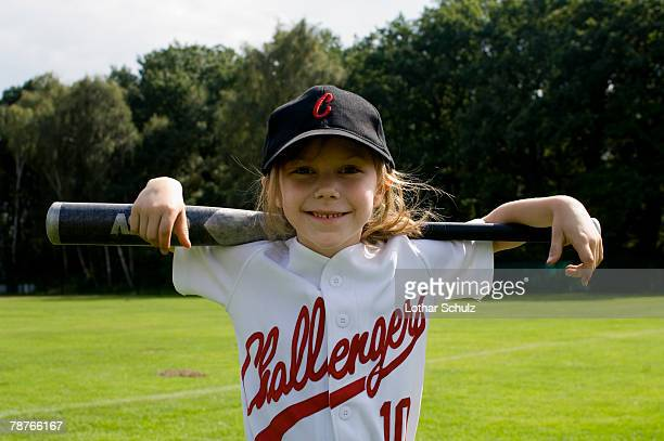 A young girl holding a baseball bat on her shoulders