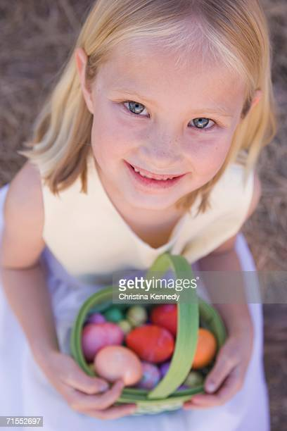 Young girl holding a basket of colorful Easter eggs