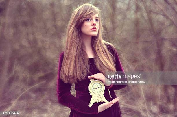 Young girl holding a clock in the woods