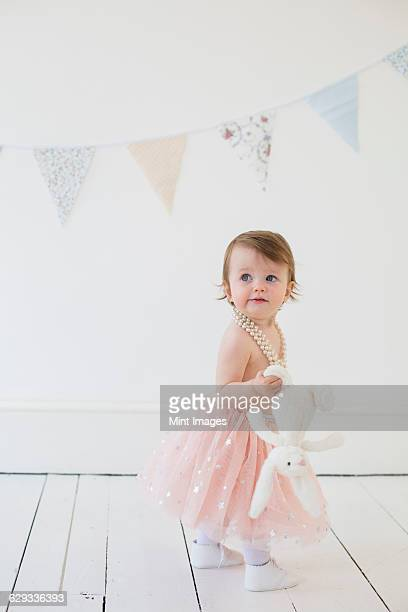 Young girl holding a cuddly toy, standing in a photographers studio, posing for a picture.