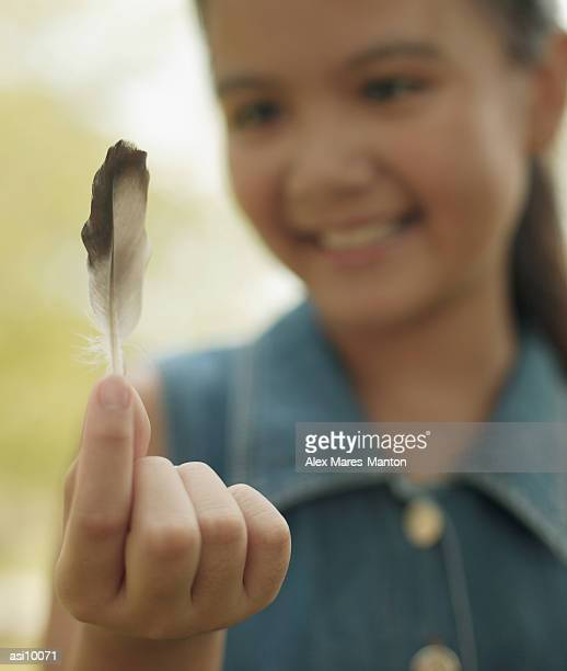 Young girl holding a feather