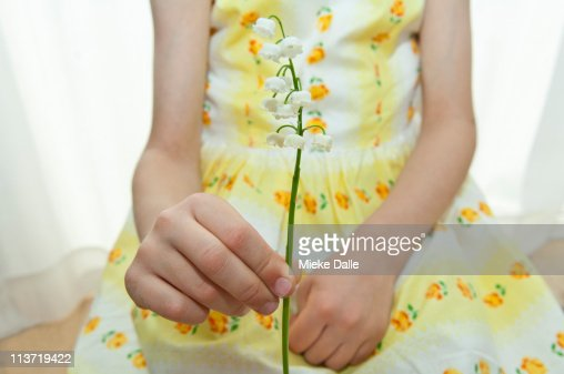 Young girl holding a lily of the valley : Stock Photo
