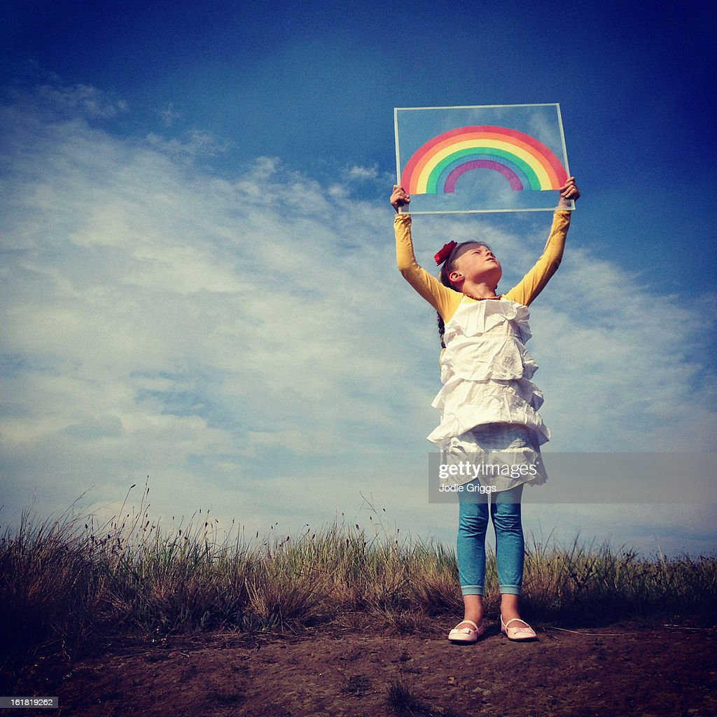 Young girl holding a paper rainbow above her head : Stock Photo