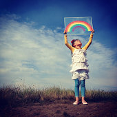 Young girl holding a paper rainbow above her head