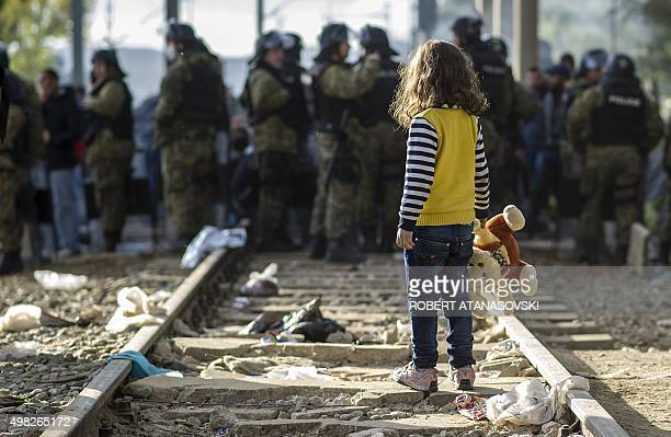 A young girl holding a stuffed animal crosses railway tracks in front of Macedonian police officers facing migrants demonstrating as they try to get...