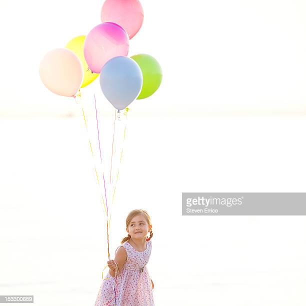 Young girl holding balloons on the beach at sunset