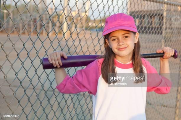 Young girl holding baseball bat behind shoulders