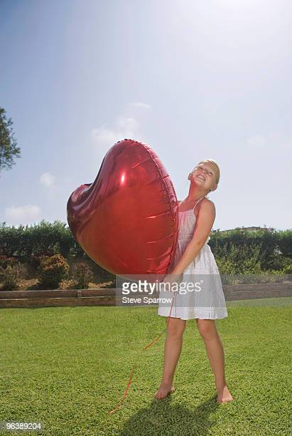 Young girl holding big red heart balloon