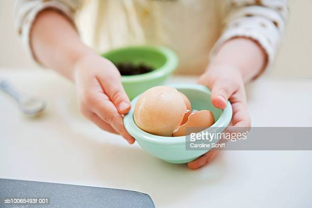 Young girl (2-3) holding bowl with eggshells, close-up