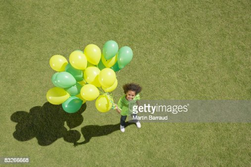 Young girl holding bunch of balloons : Stock Photo