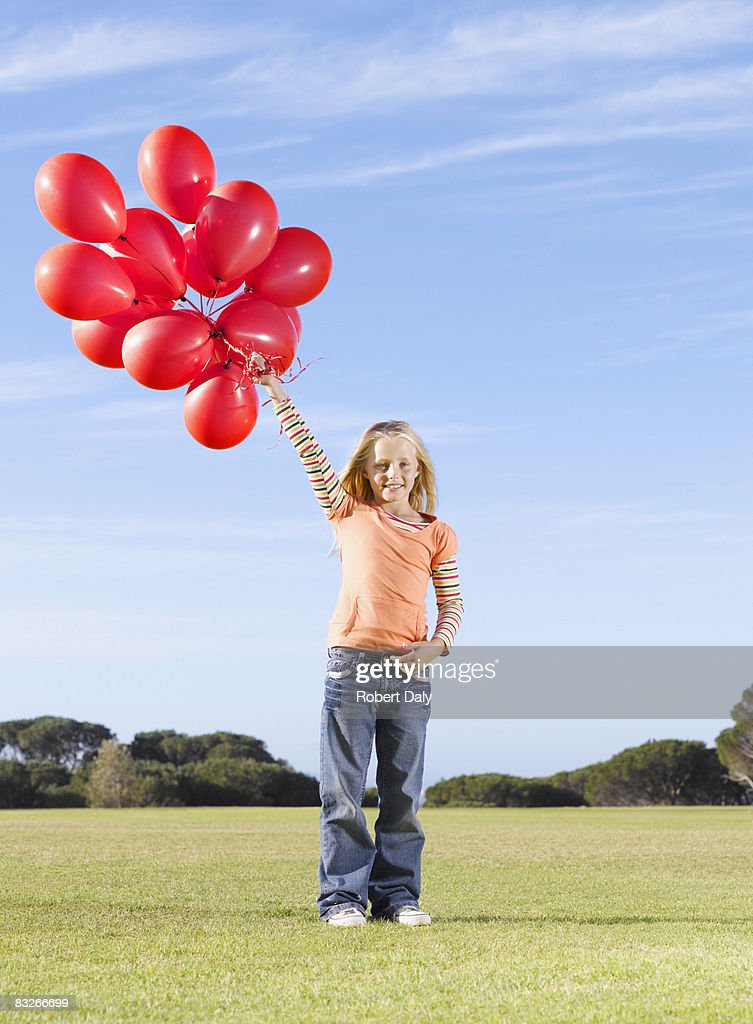 Young girl holding bunch of red balloons : Stock Photo