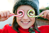 Young girl holding candy canes over her eyes