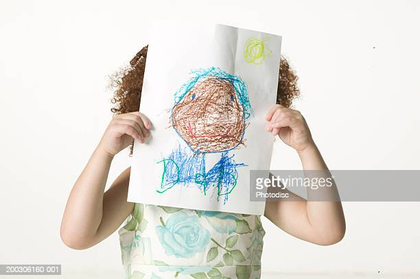 Young girl (6-7) holding crayon drawing in front of face, close-up