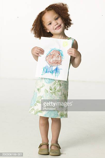 Young girl (6-7) holding crayon drawing, portrait