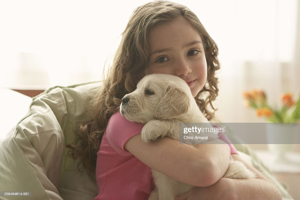 Young girl (8-10) holding dog, portrait