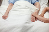 Young girl holding grandma's hand in hospital