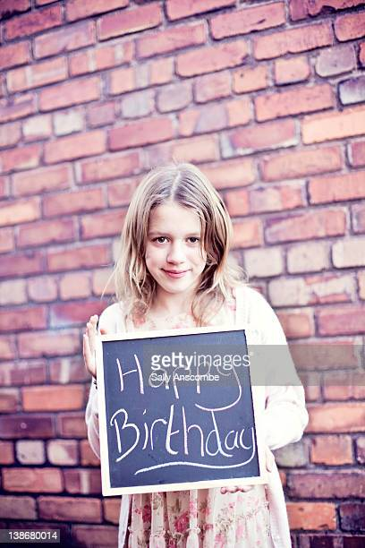 Young girl holding happy birthday sign