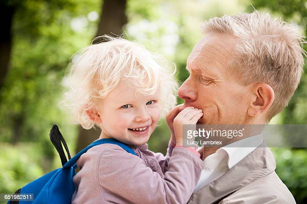Young girl holding her father's mouth shut