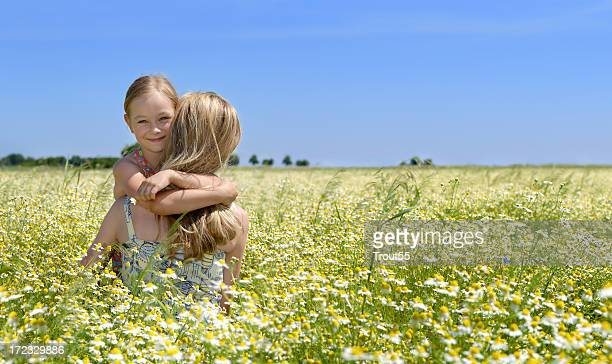 Young girl holding her mother on a flowers field