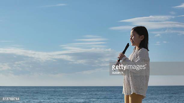 Young girl holding her recorder with a happy smile by the beach.