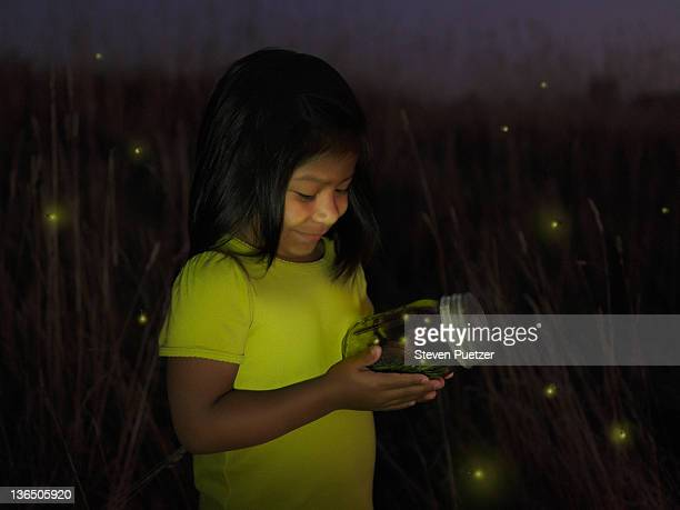 Young girl holding jar of illuminated fireflies