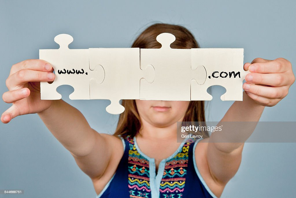 Young girl holding jigsaw puzzle pieces