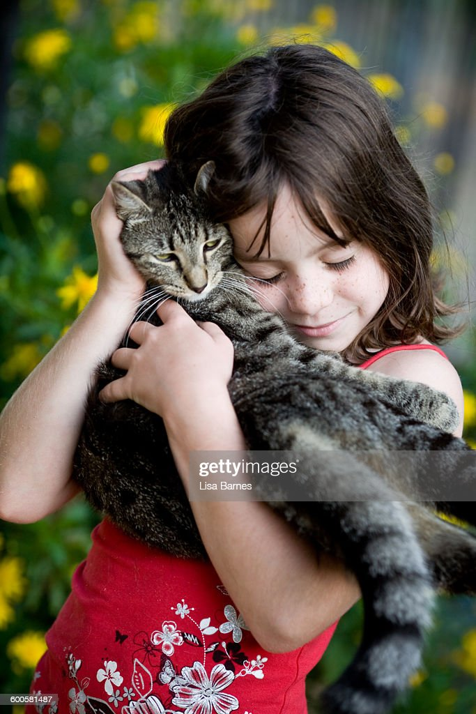 Young girl holding pet cat with eyes closed