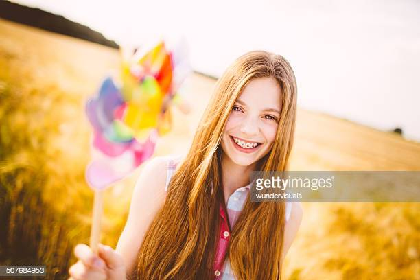 Young Girl Holding Pinwheel To Camera