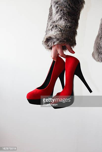Young girl holding red high heels