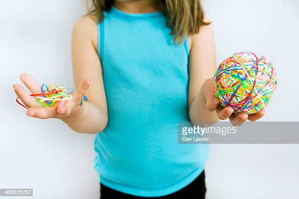 Young girl holding rubber bands