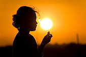 Young Girl Holding Seashell on Sunset