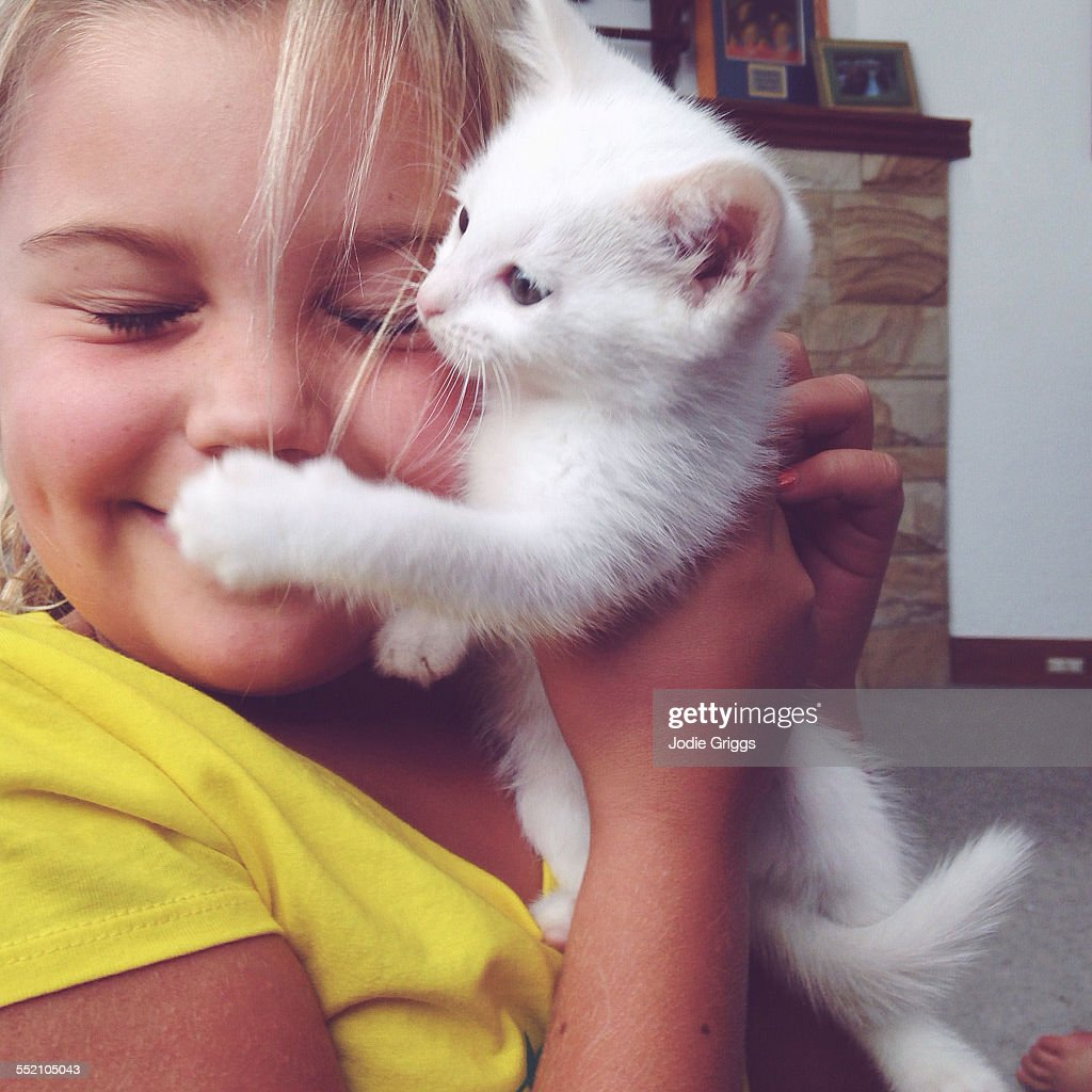 Young girl holding small kitten against face : Stock Photo