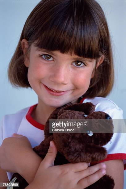 Young girl holding stuffed dog