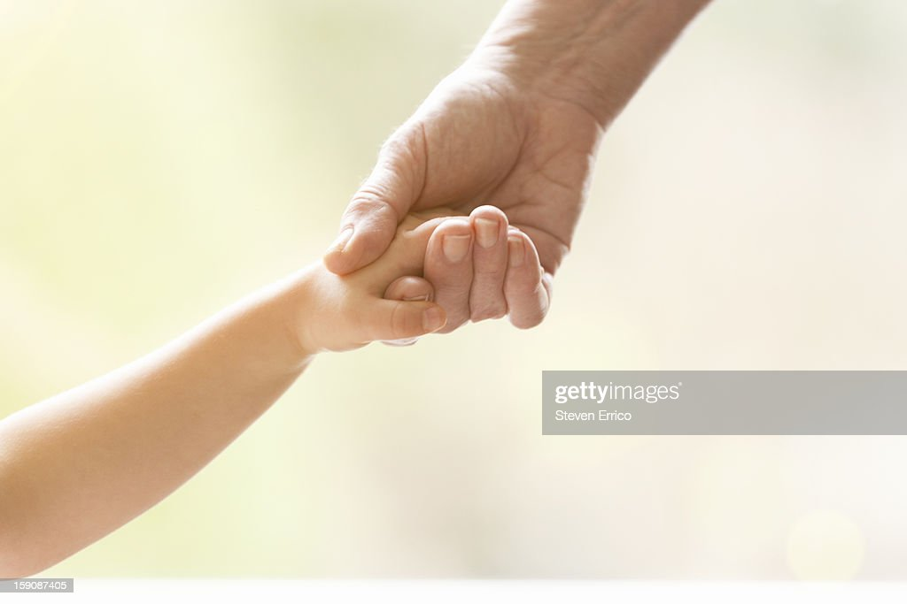 Young girl holding the hand of an elderly person : Stock Photo