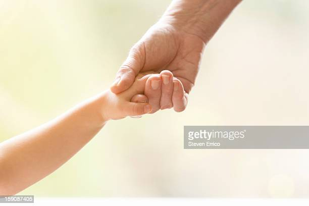 Young girl holding the hand of an elderly person