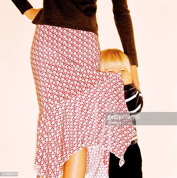 Young girl (4-6) holding the skirt of woman