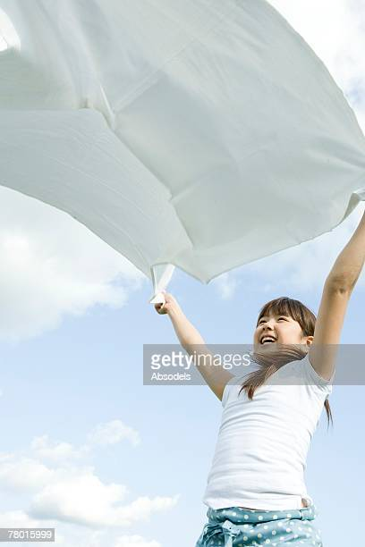 Young Girl holding white cloth outside, smiling