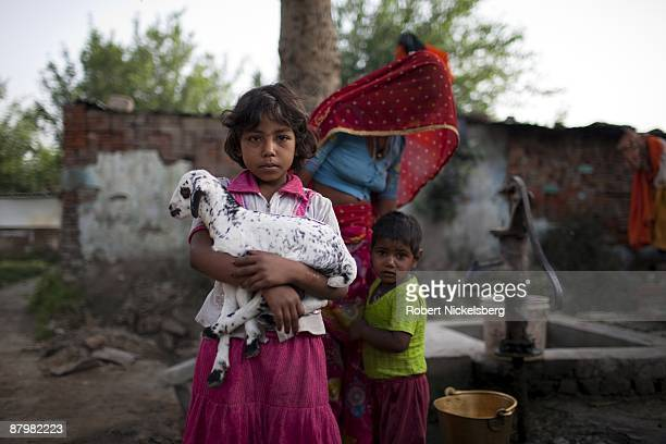 A young girl holds a baby goat in a slum area near a newly dug roadway April 22 2009 where agricultural areas she and members of twelve families have...