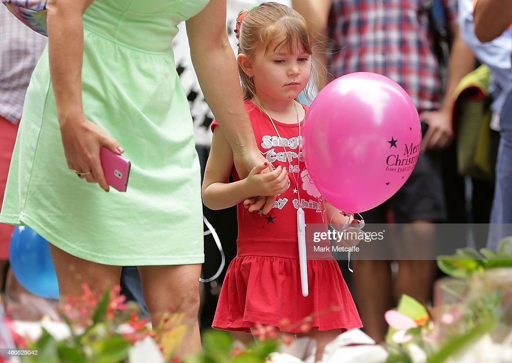 A young girl holds a balloon aloft in Martin Place on December 16 2014 in Sydney Australia Sydney siege gunman Man Haron Monis was shot dead by...