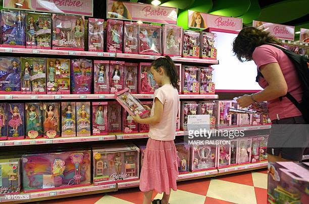 A young girl holds a Barbie doll next to a notice saying that the toy 'Barbie and Tanner' made by US toy giant Mattel which has just been recalled in...