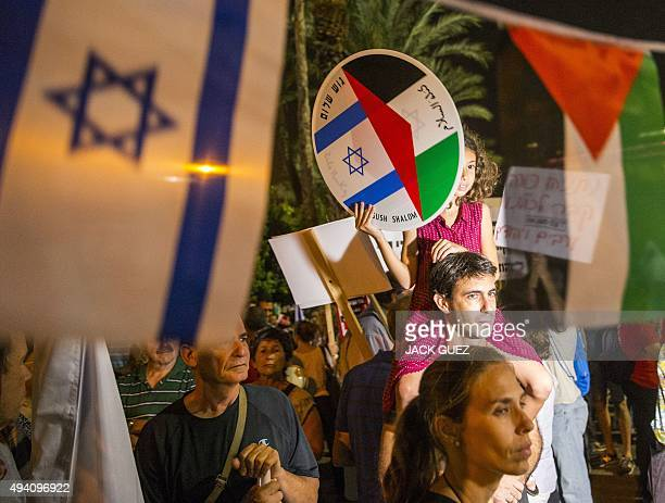 A young girl holds a bearing images of the Israeli and Palestinian flags during a Israeli leftwing activist rally demanding fresh IsraeliPalestinian...